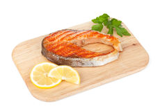Grilled salmon with lemon and herbs on cutting board Stock Photos