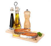 Grilled salmon with lemon and herbs on cutting board Royalty Free Stock Image