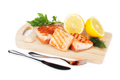 Grilled salmon with lemon and herbs on cutting board Stock Images