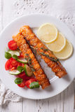 Grilled salmon with lemon and salad on a plate close-up. vertica Royalty Free Stock Photos