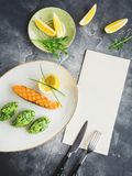 Grilled salmon with lemon slice in plate and card on table. Fish dish in restaurant Stock Photography