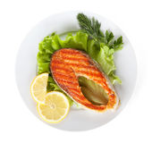 Grilled salmon with lemon slices and herbs on plate Royalty Free Stock Photo
