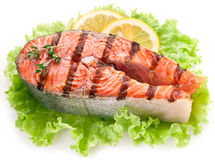 Grilled salmon and with lemon slices. Grilled salmon and with lemon slices overr lettuce leaves. Close up shot Stock Images