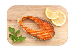 Grilled salmon with lemon slices and parsley on cutting board Royalty Free Stock Photo