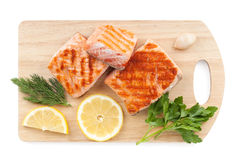 Grilled salmon with lemon slices and parsley on cutting board Stock Photos