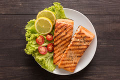 Grilled salmon with lemon,tomato on the wooden background Stock Photography