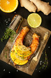 Grilled salmon, lime, orange and ginger on a black slate chalkboard Royalty Free Stock Image