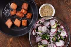 Grilled salmon with radish and spinach, served on wooden table. View from above, top studio shot. Ingredients. Broiled salmon with radish and spinach, served on Royalty Free Stock Photos