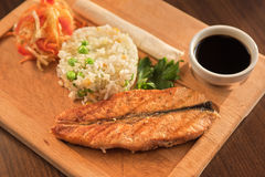 Grilled salmon with rice. And vegetables at wooden table Royalty Free Stock Photography