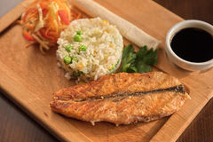 Grilled salmon with rice. And vegetables at wooden table Stock Images