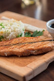 Grilled salmon with rice. And vegetables at wooden table Royalty Free Stock Image