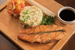 Grilled salmon with rice. And vegetables at wooden table Royalty Free Stock Photos