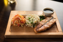 Grilled salmon with rice. And vegetables at wooden table Stock Photos