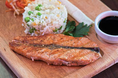 Grilled salmon with rice. And vegetables at wooden table Stock Image