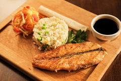 Grilled salmon with rice. And vegetables at wooden table Royalty Free Stock Photo
