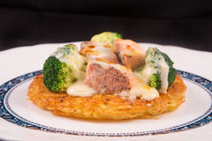 Grilled Salmon rosti with vegetables and bechamel and hollandaise. On black background Stock Photos