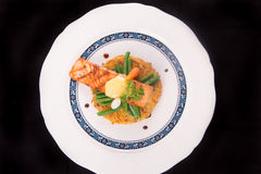 Grilled Salmon rosti with vegetables and bechamel and hollandaise. On black background Royalty Free Stock Photo
