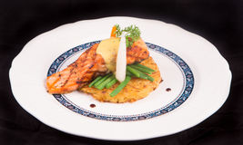 Grilled Salmon rosti with vegetables and bechamel and hollandaise. On black background Royalty Free Stock Image