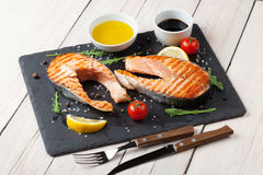 Grilled salmon, salad and condiments Royalty Free Stock Images