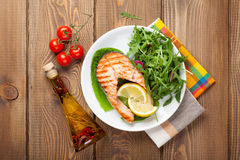 Grilled salmon, salad and condiments on wooden table Royalty Free Stock Image