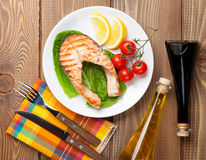 Grilled salmon, salad and condiments Royalty Free Stock Photo