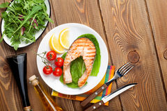 Grilled salmon, salad and condiments Royalty Free Stock Photos
