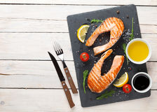 Grilled salmon, salad and condiments on wooden table Stock Photography