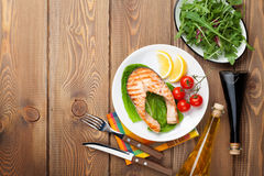 Grilled salmon, salad and condiments on wooden table Stock Photo