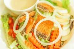 Grilled salmon with salad, onion slice rings, carrot, boiled egg and salad dressing served on white plate. Homemade and healthy. Food. Selective focus stock images