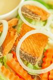 Grilled salmon with salad, onion slice rings, carrot, boiled egg and salad dressing served on white plate. Homemade and healthy. Food. Selective focus stock photography