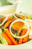 Grilled salmon with salad, onion slice rings, carrot, boiled egg and salad dressing served on white plate. Homemade, healthy food. Selective focus stock image