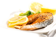 Grilled salmon with skin and vegetables on white plate Royalty Free Stock Image