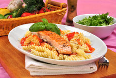 Grilled salmon on some tomato pasta. Grilled organic salmon on some tomato pasta Stock Photography