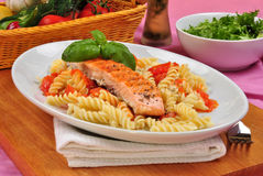 Grilled salmon on some tomato pasta. Grilled organic salmon on some tomato pasta Stock Photos
