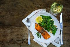 Grilled salmon with spinach an wine on a dark rustic wooden tabl Stock Images