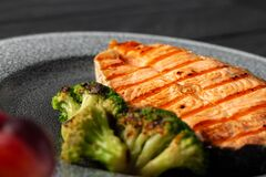Grilled salmon steak with broccoli on grey plate