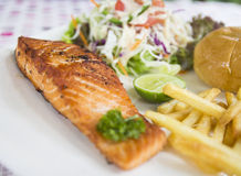 Grilled salmon steak. With bun, salad and french fried Royalty Free Stock Photos