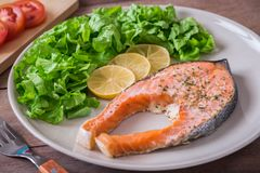 Grilled salmon steak covered with herb on plate Royalty Free Stock Photography