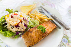 Grilled salmon steak with french fried and vegetable salad Stock Photos