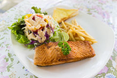 Grilled salmon steak with french fried and vegetable salad Royalty Free Stock Photo