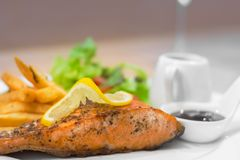 Grilled  Salmon steak. With french fries on a dish Royalty Free Stock Photography