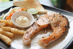 Grilled salmon steak with french fries and toast. Royalty Free Stock Images