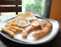 Grilled salmon steak with french fries and toast. Royalty Free Stock Photos