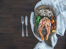 Grilled salmon steak with fresh herbs, roasted mushrooms, cherry Stock Images