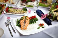 Grilled salmon steak with green beans, on decorated dining table Stock Image