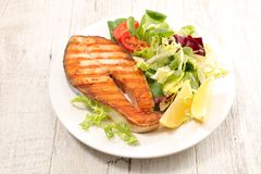 Grilled salmon steak. And salad Stock Photos