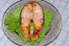 Grilled salmon steak laid on a transparent plate stock photography