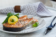 Grilled Salmon steak with lemon and herbs. Grilled Salmon steak with lemon and herbs on white dish. Healthy food concept Stock Photo