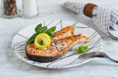 Grilled Salmon steak with lemon and herbs. Grilled Salmon steak with lemon and herbs on white dish. Healthy food concept Royalty Free Stock Images