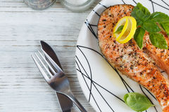 Grilled Salmon steak with lemon and herbs. Grilled Salmon steak with lemon and herbs on white dish. Healthy food concept Royalty Free Stock Photo